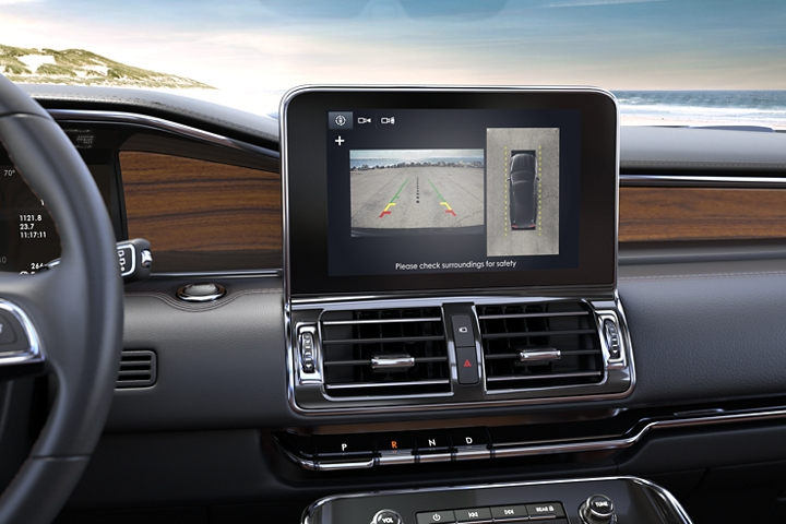 A 2020 Lincoln Navigator is parked on a sunny beach and we see a bright 10 inch L C D screen displaying the birds eye view of the 3 60 degree camera
