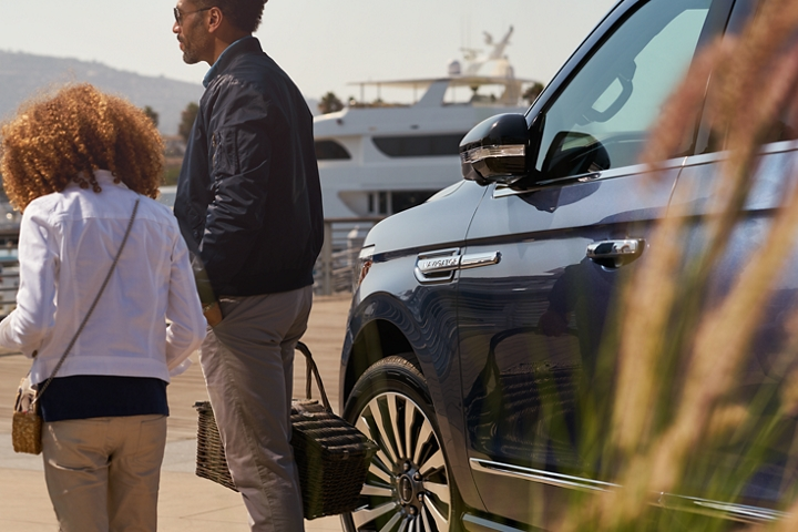 A little girl and dad holding a picnic basket walk away from a 2020 Lincoln Navigator with its side view mirror folded and a white yacht in the back