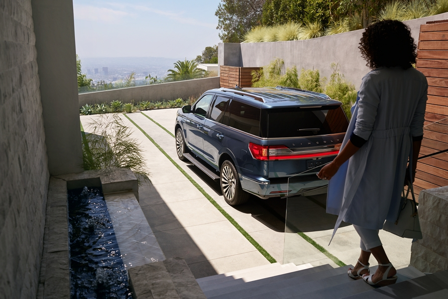 A woman approaches a 2020 Lincoln Navigator outside a geometric loft entrance as her Personal Profile settings are recognized and being adjusted