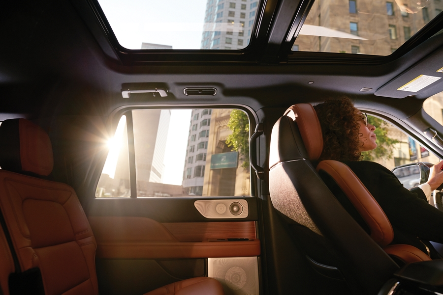 A woman in the drivers seat looks peaceful as sunlight cuts through the windows and illuminates the interior with soft light and serene energy