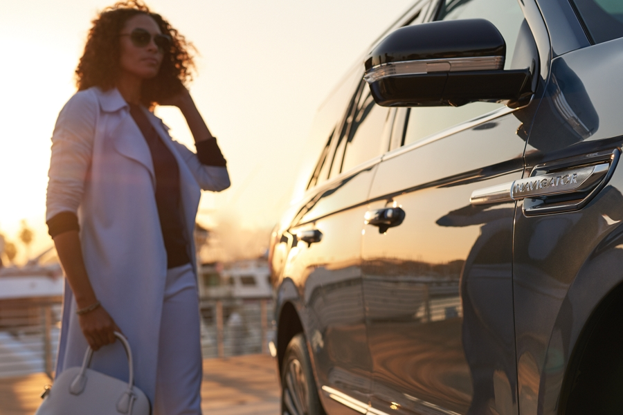 A woman stands next to a 2020 Lincoln Navigator at a marina as her silhouette is illuminated by the setting sun and reflected in the exterior