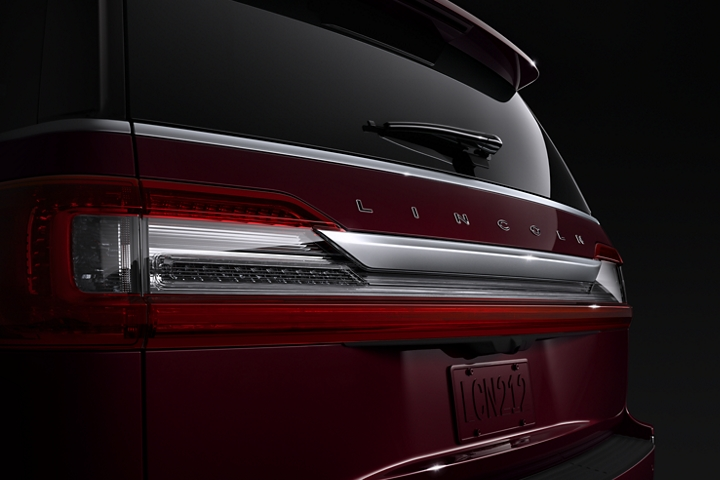 The rear of a 2020 Lincoln Navigator in Burgundy Velvet Destination theme shows bright red brake lights that meld with the red hue of the body
