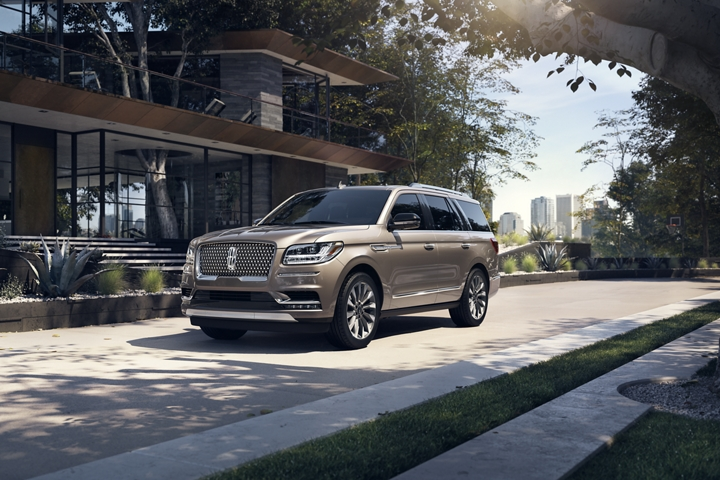 A 2020 Lincoln Navigator in Iced Mocha is parked in front of a modern home surrounded by nature and tucked away from a big city nearby