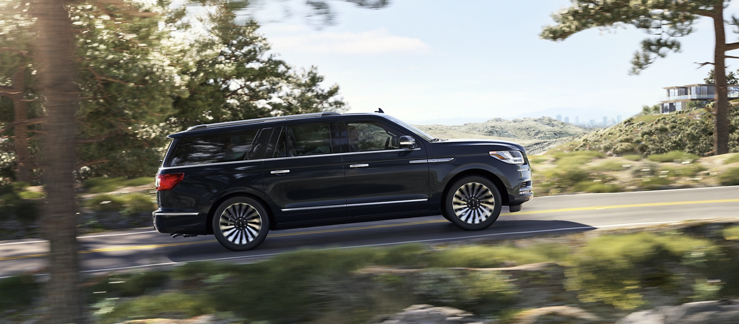 A 2020 Lincoln Navigator in Infinite Black is being smoothly guided up an incline surrounded by greenery with a cityscape fading away in the back