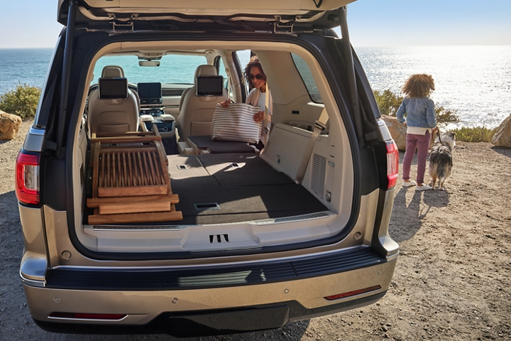 The second and third rows of a 2020 Lincoln Navigator are folded flat to show cargo space as a mother unloads a bag on a beach with sparkling waters