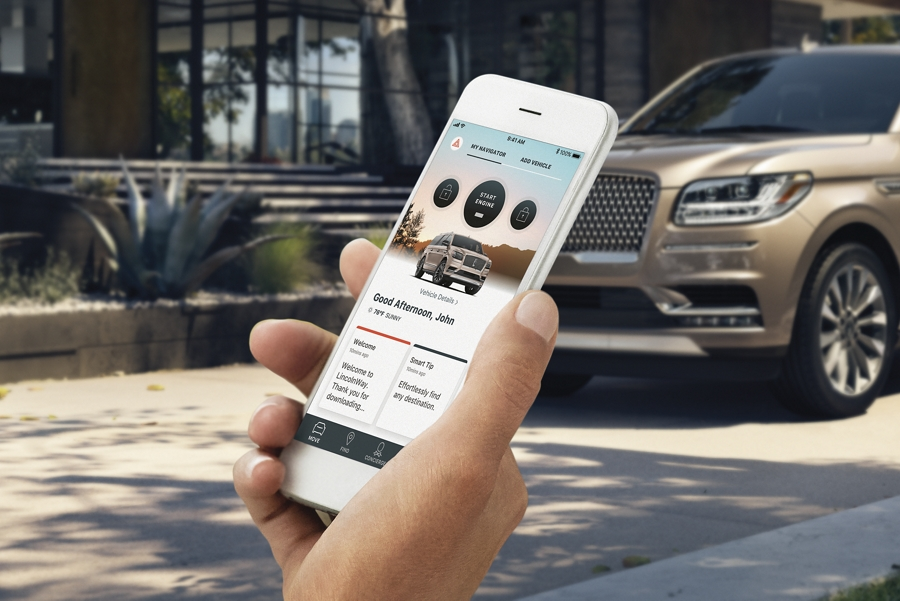 A hand is holding a phone with the Lincoln Way App on screen with a 2020 Lincoln Navigator parked in the background in front of a modern loft