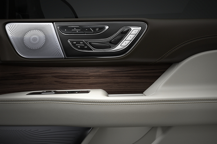 A close up of perfect position seat controls and detail of wood inlay show off the polished look through a pallet of chrome black brown and cream