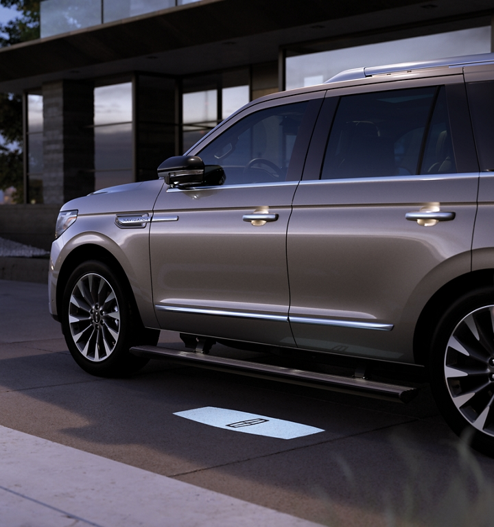 A 2020 Lincoln Navigator parked in front of a glass house is projecting a welcome mat and glowing with available Lincoln Embrace