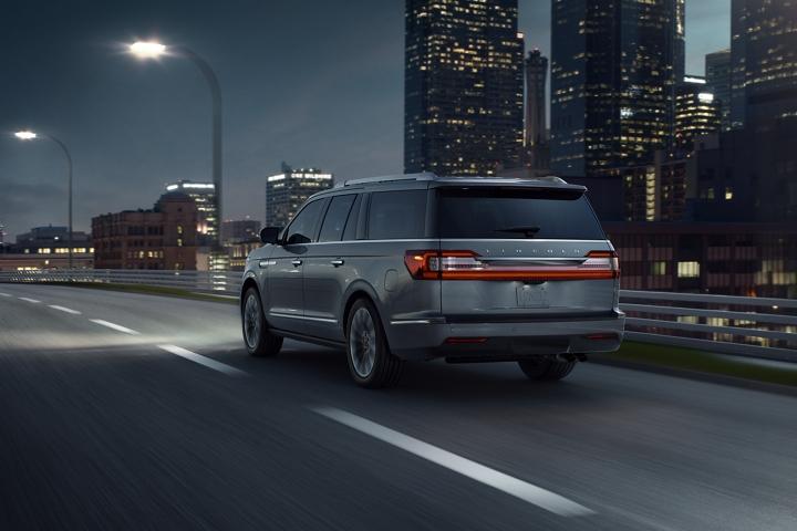 Para demostrar el sistema de mantenimiento de carril, una Lincoln Navigator 2020 anda por una carretera con marcas de carril, pasando rascacielos