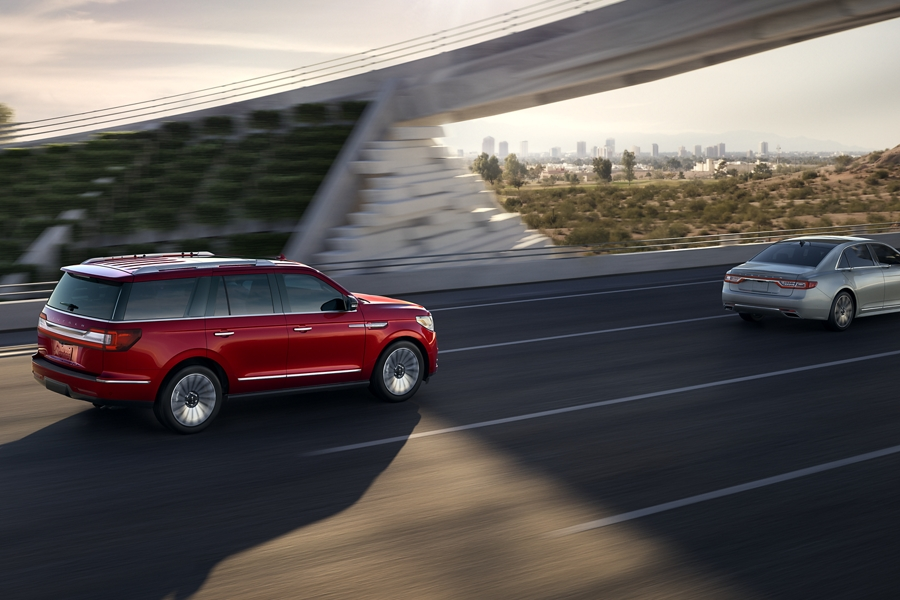 A 2020 Lincoln Navigator in Red Carpet is being driven along a highway as it maintains a safe distance behind the car in front of it