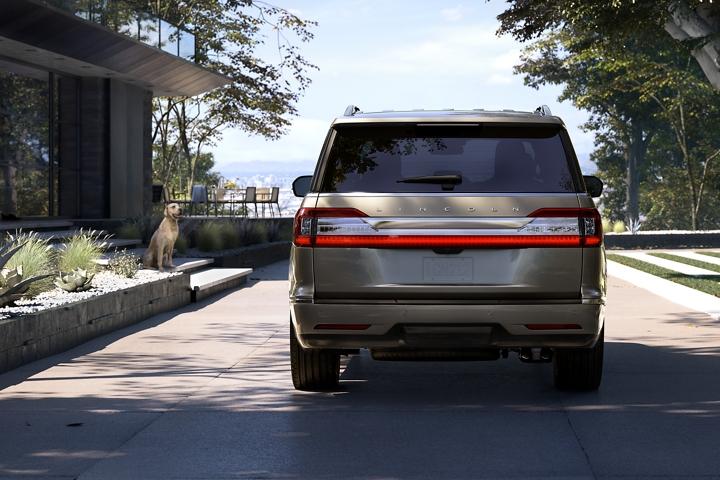 Se muestra una Lincoln Navigator 2020 estacionada en una casa moderna mientras un golden retriever está sentado y espera en los escalones de la casa