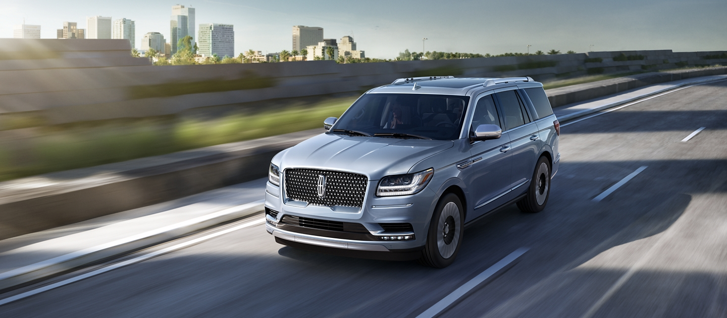 A 2020 Lincoln Black Label Navigator in Chroma Crystal Blue is being driven on a freeway against the blur of sunlit greenery and a cityscape