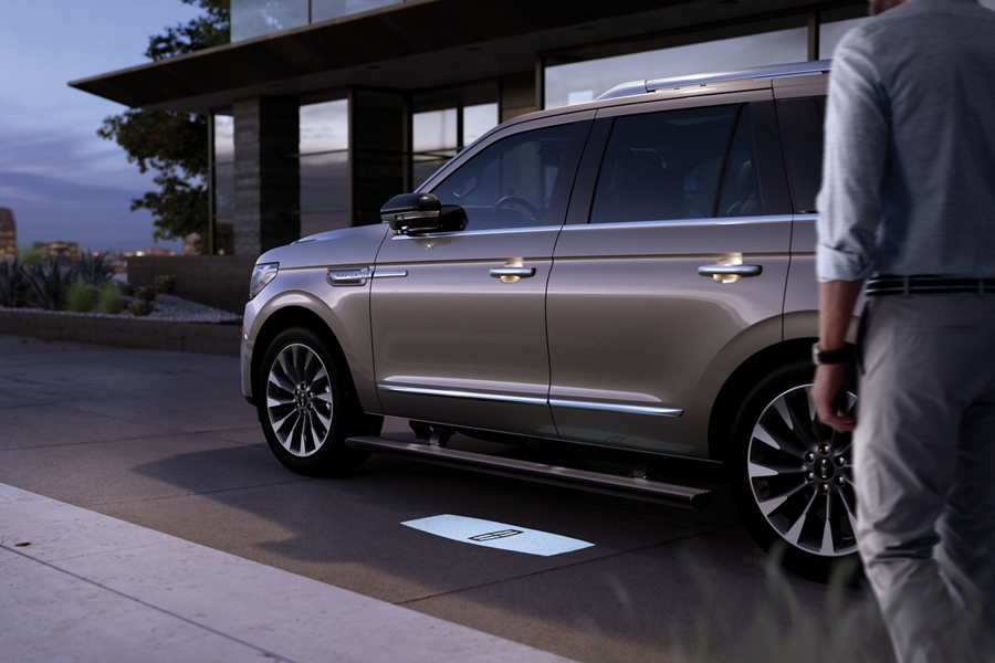 A 2020 Lincoln Navigator with extended running boards is parked in front of a glass house glowing against the fading light of day