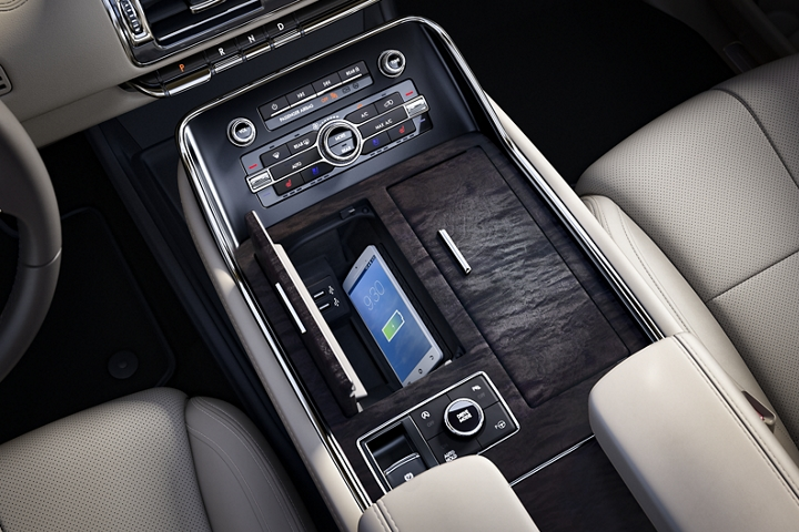 A compatible mobile phone is shown actively charging on the inductive charging system inside a sleek hideaway compartment within the center console