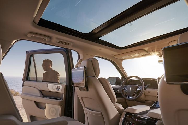 Se muestra un cielo azul a través de las ventanas y el techo corredizo mientras las pantallas montadas en la parte trasera de los asientos de la primera fila reflejan los alrededores