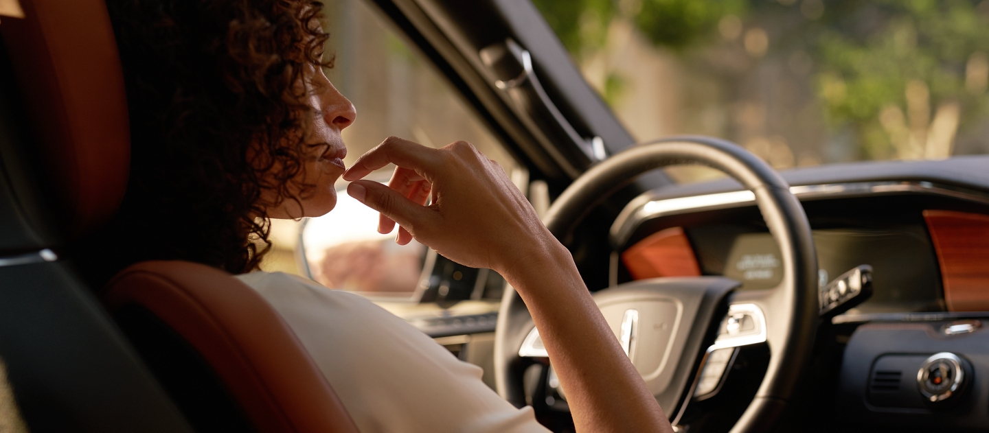 A female driver is thoughtfully looking at her center screen as soft sunlight spills through the windows