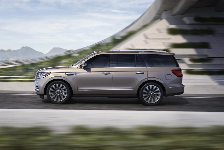 La Lincoln Navigator 2020 en moka helado emerge desde las sombras de un paso elevado con sus curvas exteriores iluminadas con la luz de un día esplendoroso
