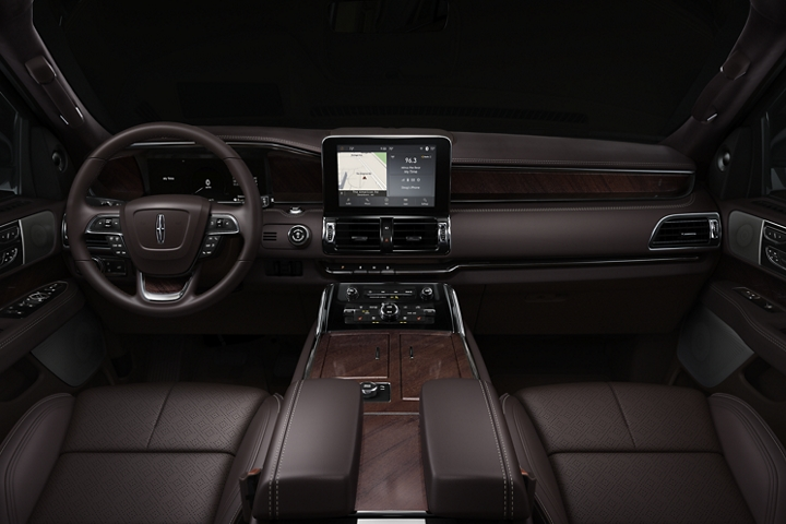 The front row of a 2020 Lincoln Black Label Navigator in the Destination theme shows warm rich leather and wood detail as well as spacious comfort