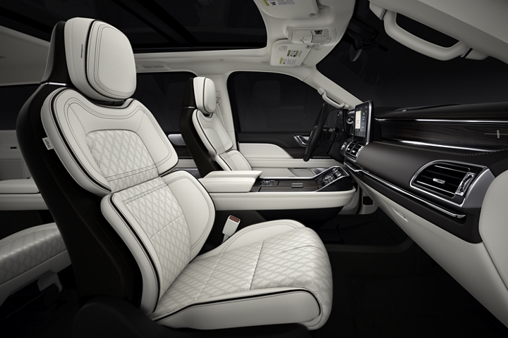 The interior of a 2020 Lincoln Black Label Chalet Navigator shows off the dramatic contrast of light and dark elements and textured materials
