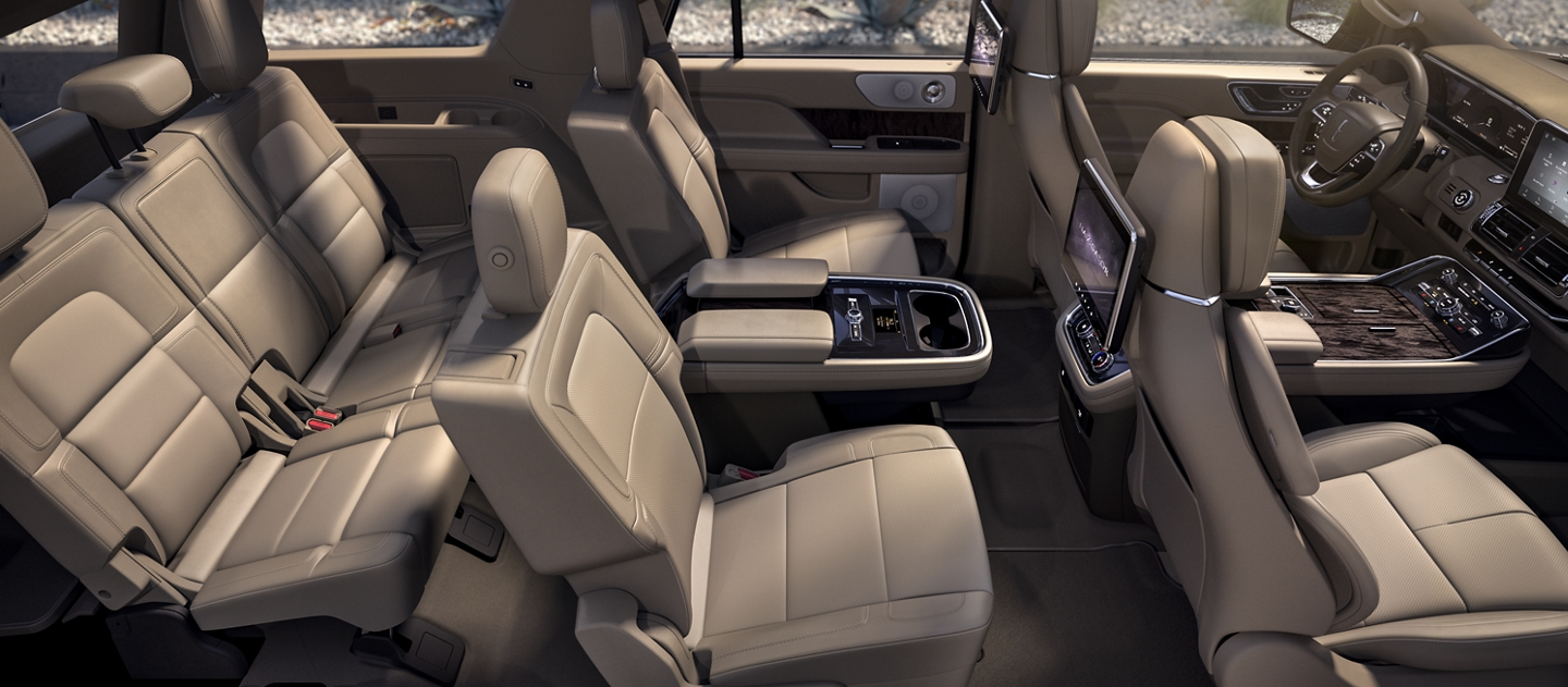 A wide shot of the 2020 Lincoln Navigator interior is bathed in soft inviting light and shows off the spacious design of second and third row seating