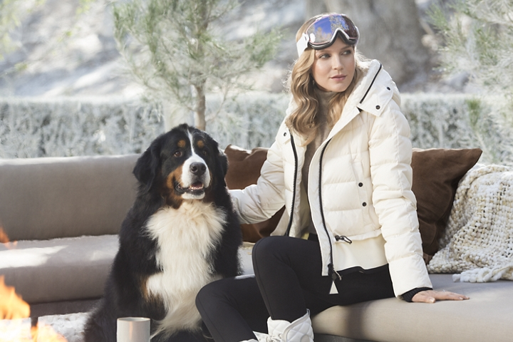 A woman wearing ski gear is shown taking a break with her dog in the sun on an outdoor couch representing the inspiration for the Chalet theme