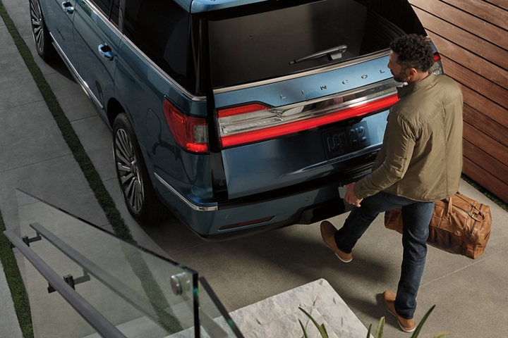 A man carrying a brown duffel bag and phone is kicking his foot under the rear bumper of a 2020 Lincoln Navigator to open the hands free liftgate