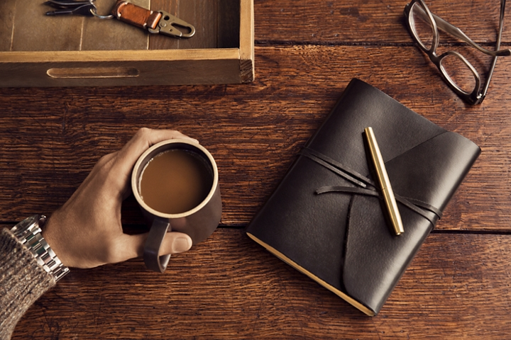 A hand is holding a mug of coffee on a wooden desk next to glasses and a dark leather bound travel journal to capture their insights and adventures